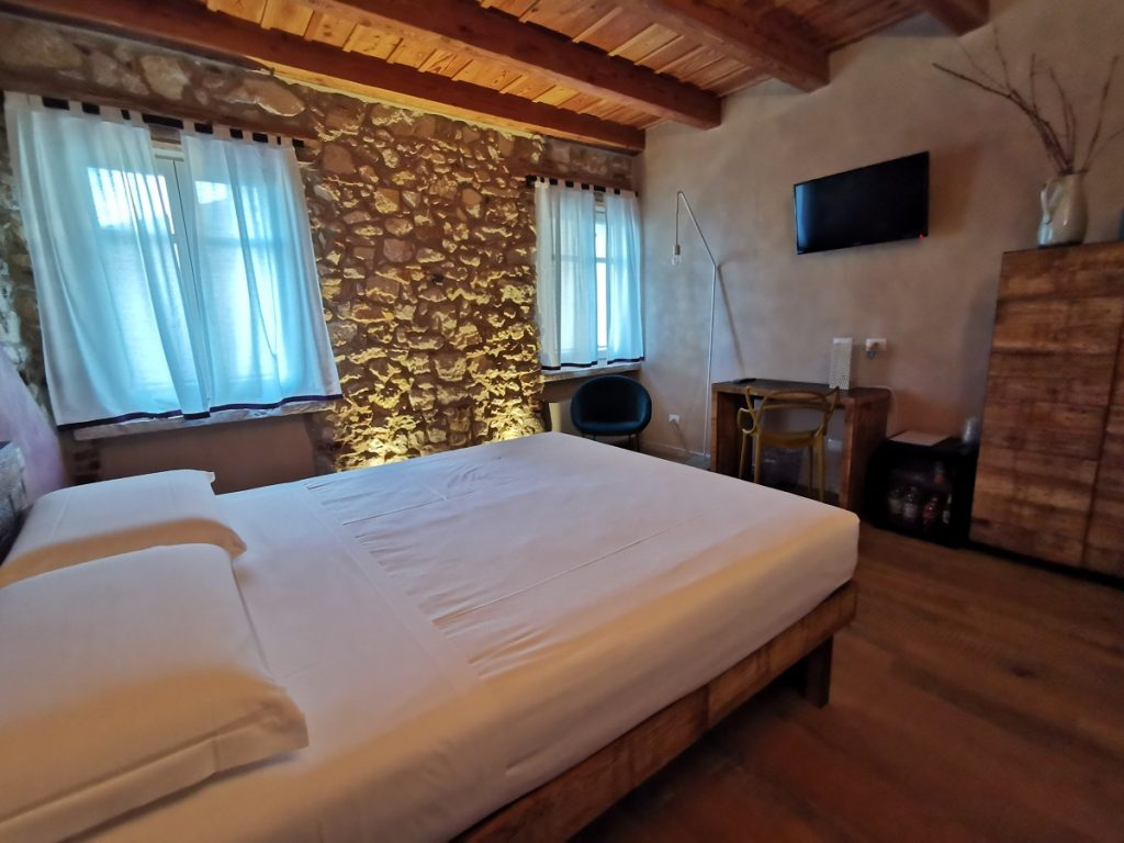 Stanza La Vigna a Corte Formigar con letto, mattoni a vista e dettagli in legno e cortèn