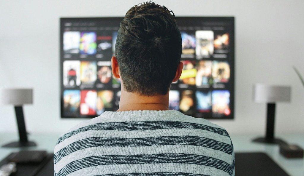 Uomo che guarda serie TV per migliorare il suo inglese